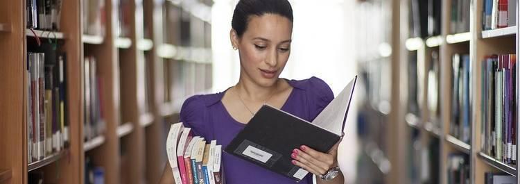 Een vrouw die in de bibliotheek aan het lezen is