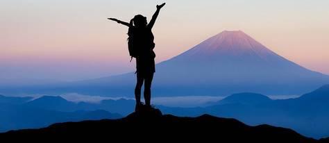 Een vrouw die met armen omhoog op een berg staat