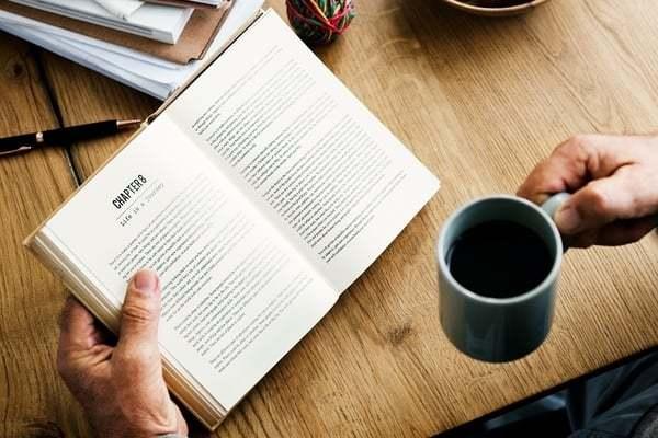 Iemand ie een boek vast houdt en een kop koffie
