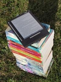 Een e-reader die bovenop een stapel boeken ligt