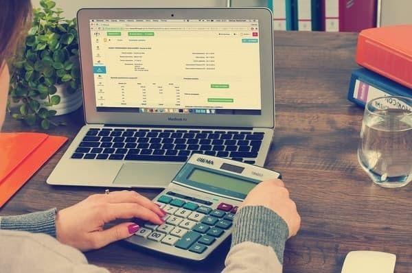 Een vrouw die een rekenmachine gebruikt bij een laptop