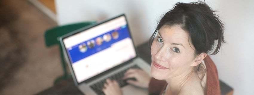 Een vrouw die omkijkt terwijl ze achter een laptop zit