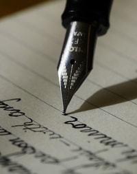 Een pen die op een stuk papier aan het schrijven is