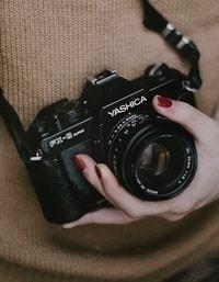 Een vrouwenhand die een camera vast houd