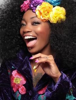Een lachende vrouw met bloemen in haar haar