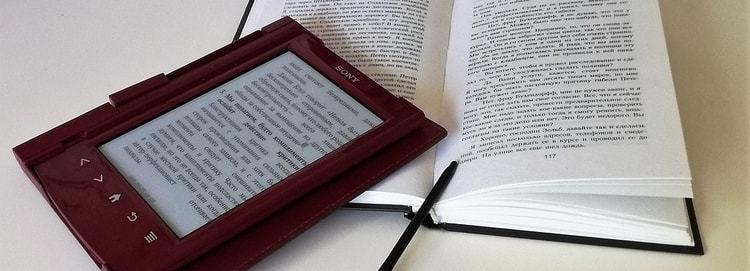 Een e-reader die op een boek ligt