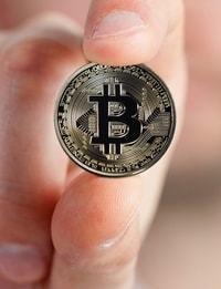 Een hand die een bitcoin munt tussen de vingers houd