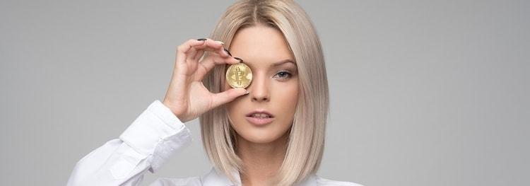 Vrouw die een bitcoin munt voor haar oog heeft