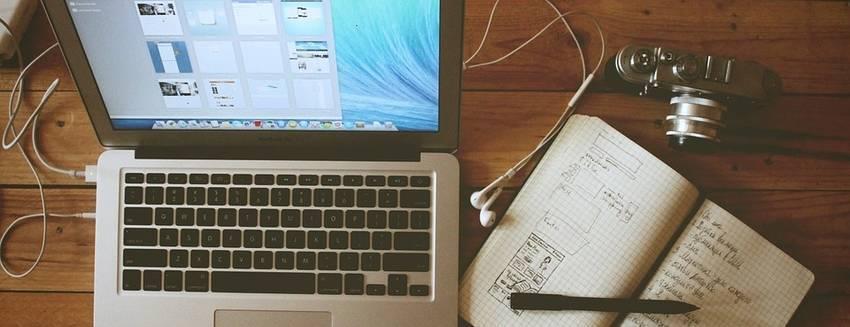 Een laptop met daarnaast een notebook