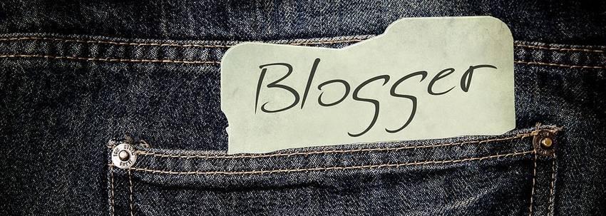 Een papier waar Blogger op staat in een broekzak