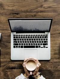 Iemand die een kop koffie vast heeft voor een laptop