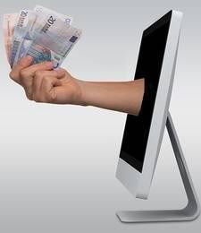 Een hand die uit een computer komt met briefgeld er in
