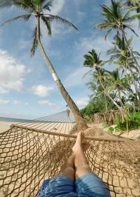 Iemand die op het strand in een hangmat ligt bij een palmboom