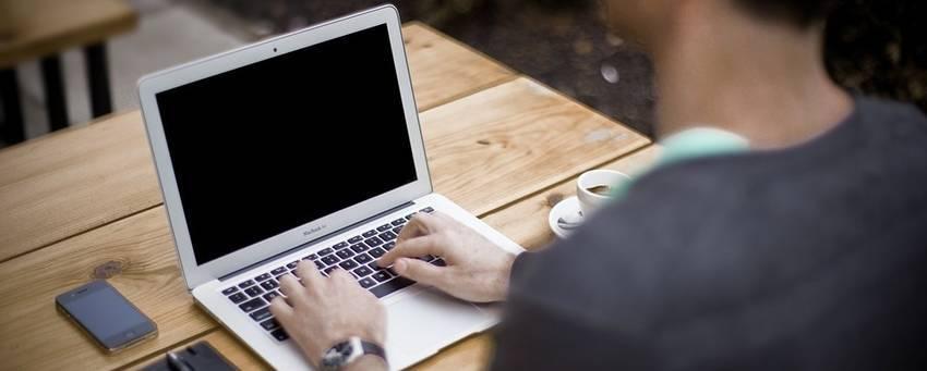 Een man die aan typen is op zijn laptop