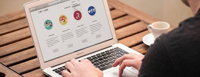 Een man die achter zijn laptop een verkooppagina maakt