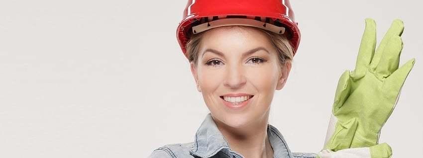 Een vrouw met een bouwhelm op en handschoenen aan