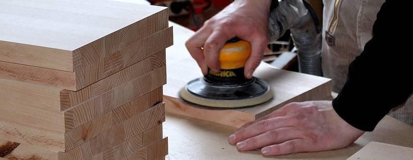 Een man die hout aan het schuren is met een machine