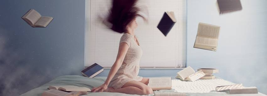 Een vrouw die met haar haar schud en de boeken in het rond vliegen