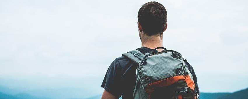 Een man met een rugtas die uitkijkt over de bergen
