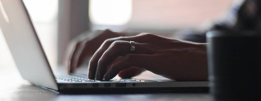 Twee handen die aan het schrijven zijn op een laptop